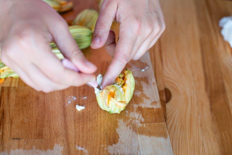 Preperation di Fried Zucchini Flowers, mani della donna farcente con il formaggio di ricotta fotografia stock libera da diritti