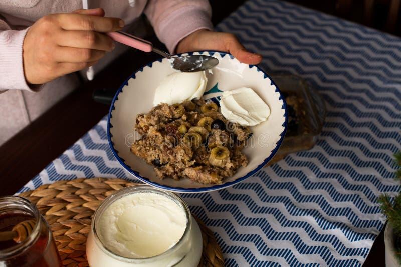 preperation van gebakken havermeel met banaan, bosbessen, okkernoot en rozijnen gediend met yoghurt en honing Druipende honing pu stock afbeeldingen