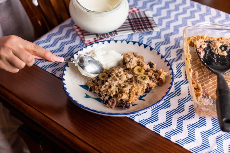 preperation van gebakken havermeel met banaan, bosbessen, okkernoot en rozijnen gediend met yoghurt en honing Druipende honing pu royalty-vrije stock foto's