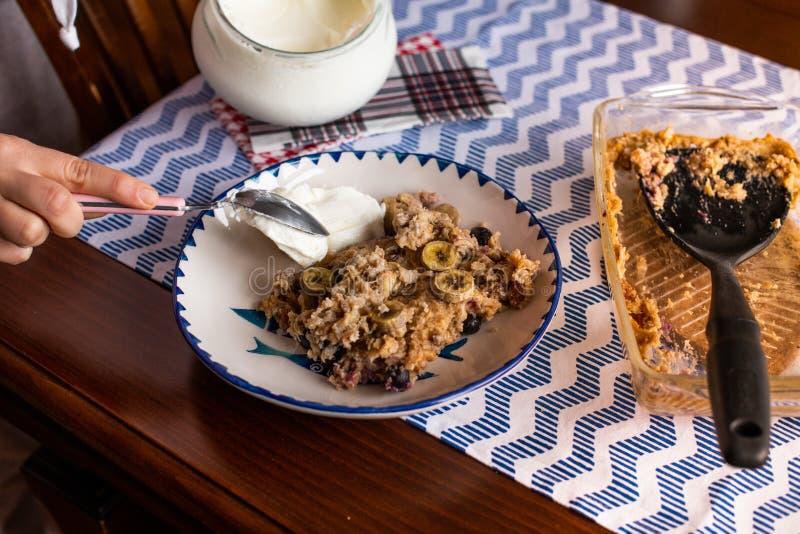preperation van gebakken havermeel met banaan, bosbessen, okkernoot en rozijnen gediend met yoghurt en honing Druipende honing pu stock fotografie