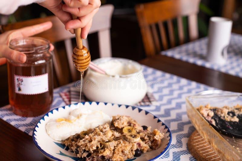 preperation van gebakken havermeel met banaan, bosbessen, okkernoot en rozijnen gediend met yoghurt en honing Druipende honing pu royalty-vrije stock afbeelding