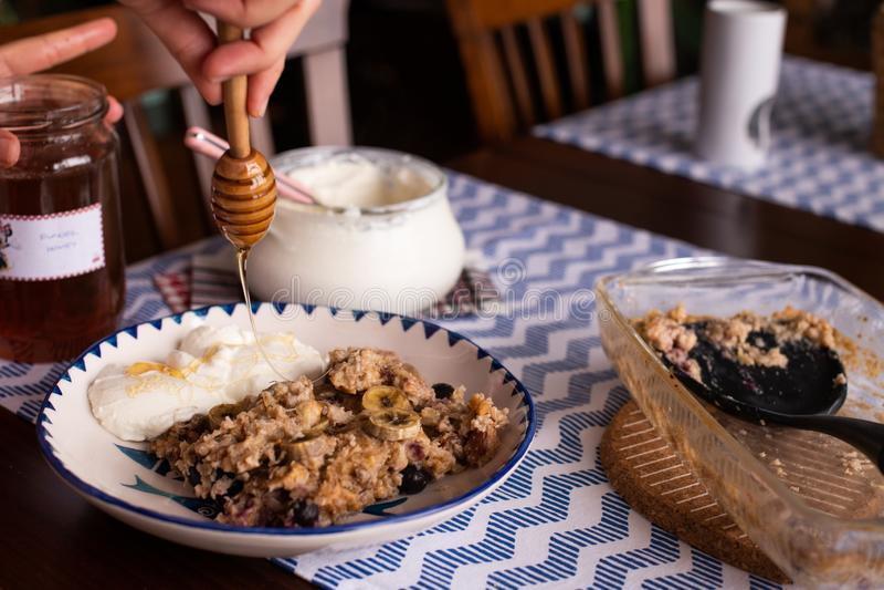 preperation van gebakken havermeel met banaan, bosbessen, okkernoot en rozijnen gediend met yoghurt en honing Druipende honing pu royalty-vrije stock fotografie