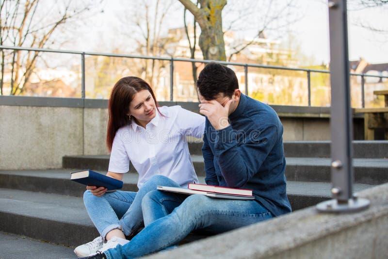 Preplexedstudent die voor examen voorbereidingen treffen stock afbeelding