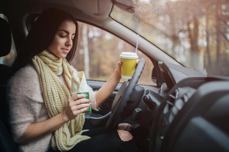 PrePretty woman eating food and driving in her car. Fall vacation, holidays, travel, rty woman eating food and driving in her car. stock photo