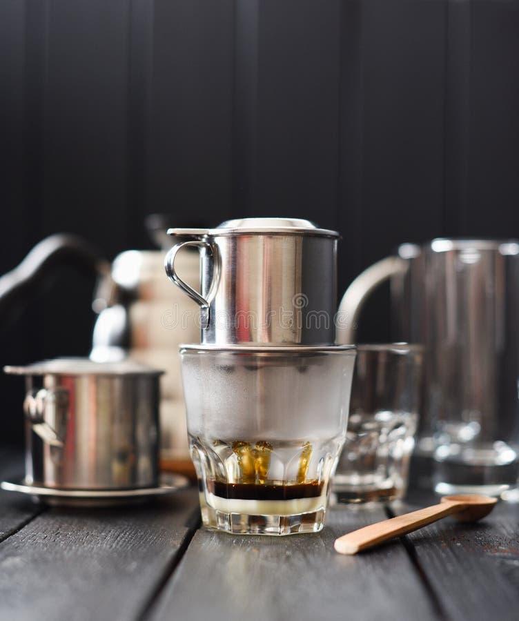 Preraring滴水咖啡越南样式 从咖啡壶phin的热的无奶咖啡水滴到在黑背景的玻璃里 免版税库存照片
