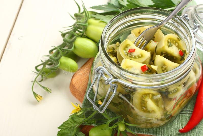 Prerogative verdi casalinghe dei pomodori in barattolo di vetro fotografia stock