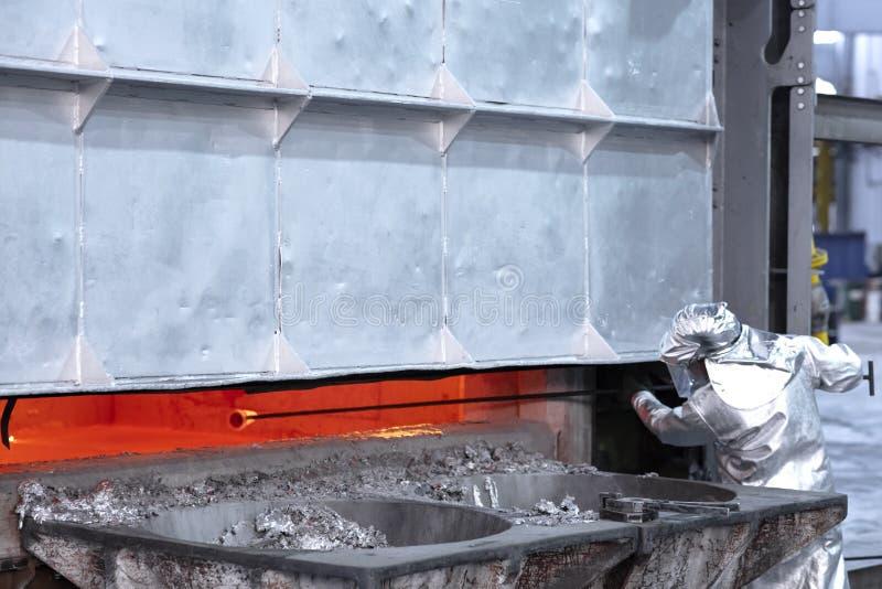 Presa del lavoratore campioni in una fonderia di alluminio immagini stock