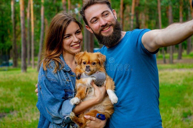 Presa dell'autoritratto Le belle coppie felici dell'giovane-adulto che spendono il tempo sull'erba con uno sveglio bianco fanno fotografia stock libera da diritti