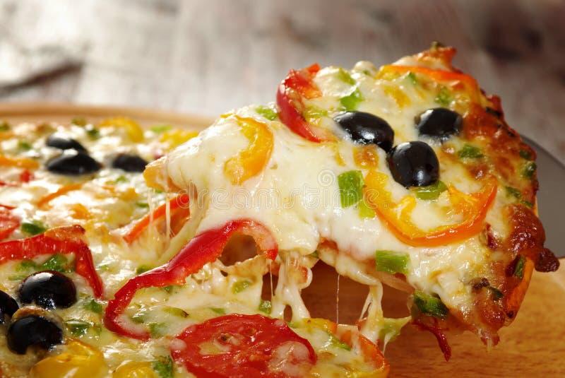 Presa della fetta di pizza, sgocciolatura fusa del formaggio fotografia stock