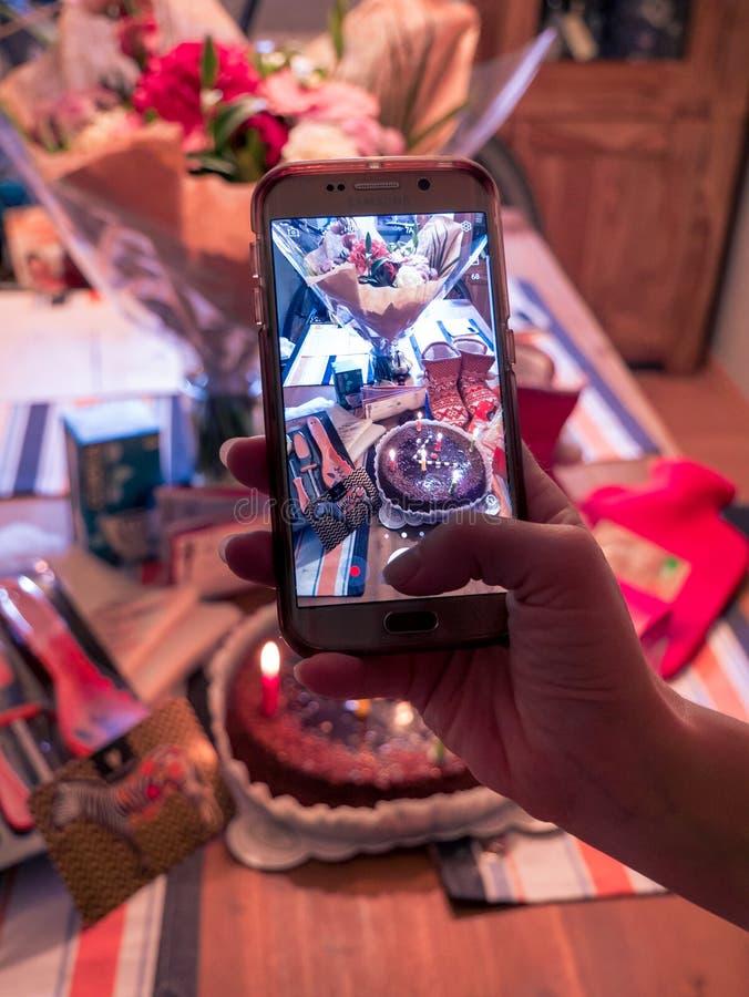 Presa della foto dei regali di compleanno con lo smartphone fotografia stock libera da diritti
