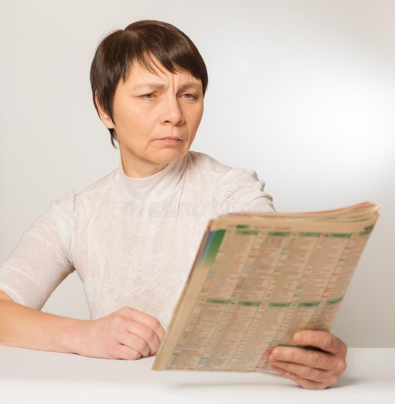 presbyopia Ung kvinna med långt hårsammanträde i läsning för fönsterplats arkivbild