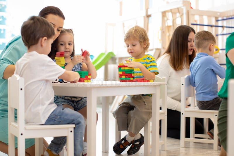 Preschool учитель с детьми играя с красочными деревянными воспитательными игрушками на детском саде стоковое фото
