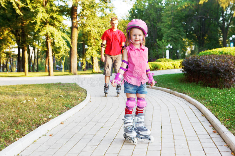 Preschool beginner in roller skates. In front, and dad behind royalty free stock photos