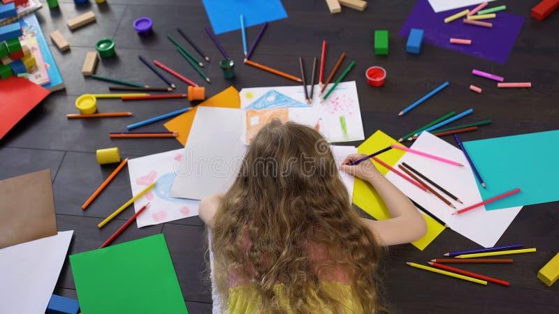 Preschool blond dziewczyna rysunek z kolorowymi ołówkami przy wolnym czasem, dzieciństwo zdjęcia royalty free