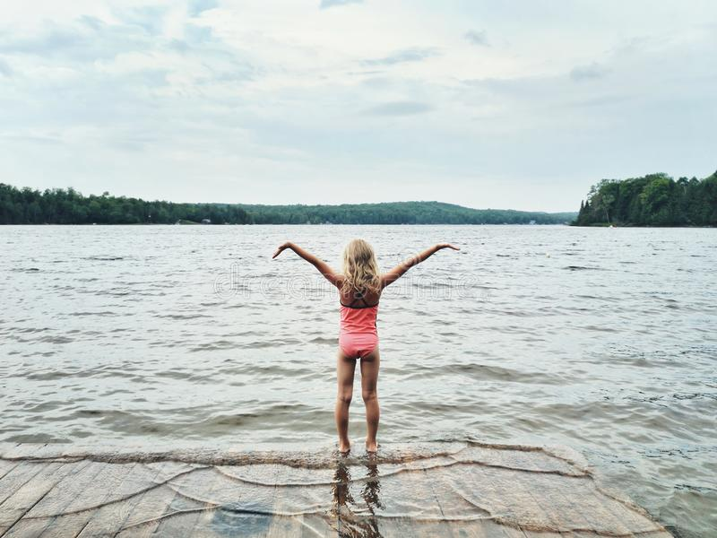 Preschool blonde girl in pink swimsuit standing on wooden lake river dock stock photo