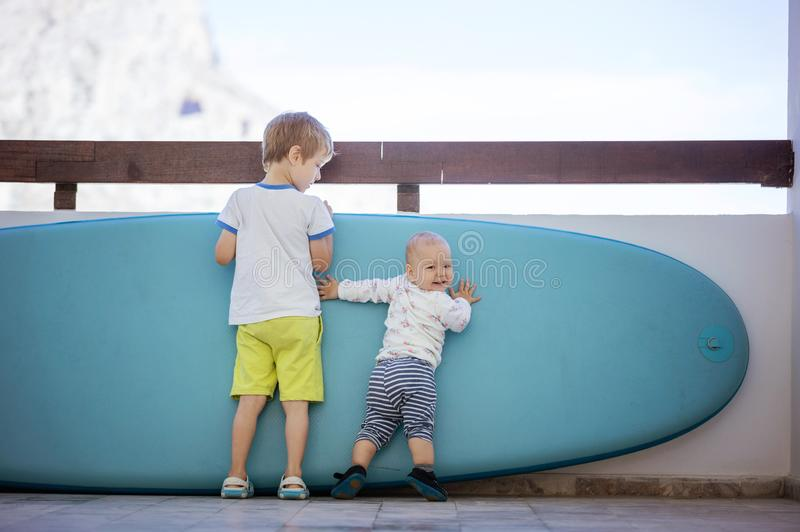 Preschool boy and baby girl standing at sup board royalty free stock photos