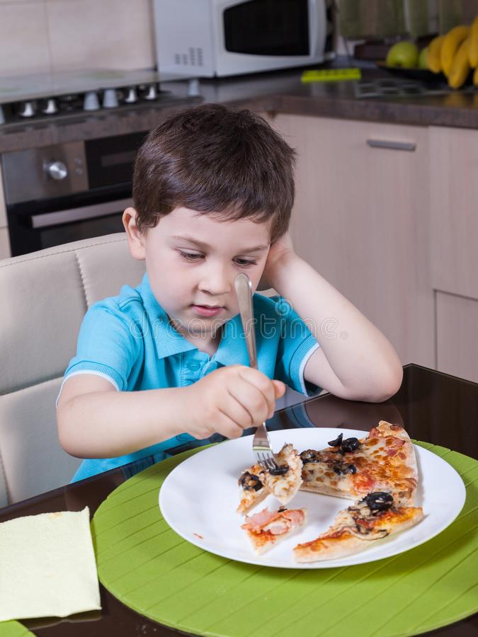 Preschool boy eat pizza. In the kitchen stock image