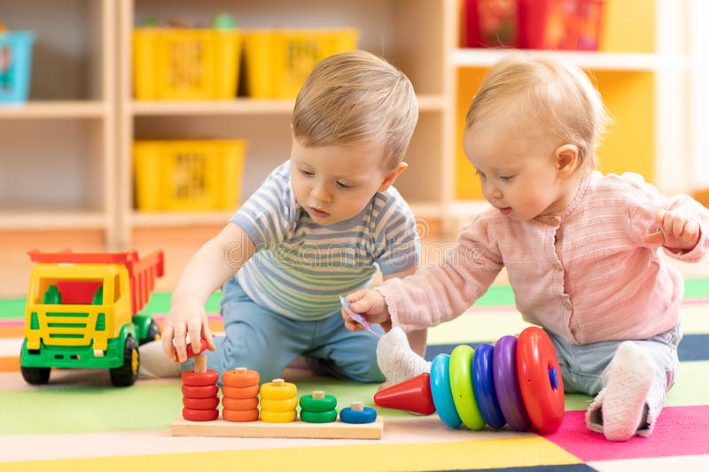 Preschool boy and girl playing on floor with educational toys. Children at home or daycare. royalty free stock photography