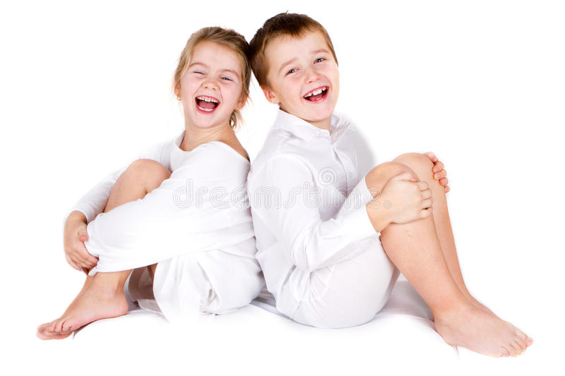 Preschool boy and his sister. Happy siting and laughing preschool boy and his sister on white background stock image
