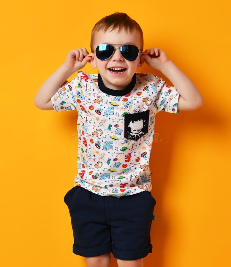 Preschool boy kid standing in blue sunglasses and t-shirt happy smiling on yellow royalty free stock photos