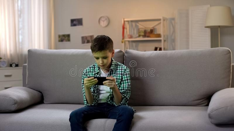 Preschool boy procrastinating and playing game on smartphone, gadget addiction. Stock photo royalty free stock image