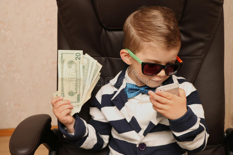 Preschool boy. Talking on the phone and holding a cash dollar stock image