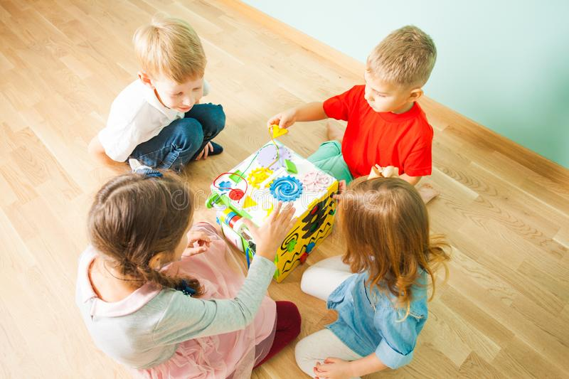 Kids playing on floor with educational toys stock photo