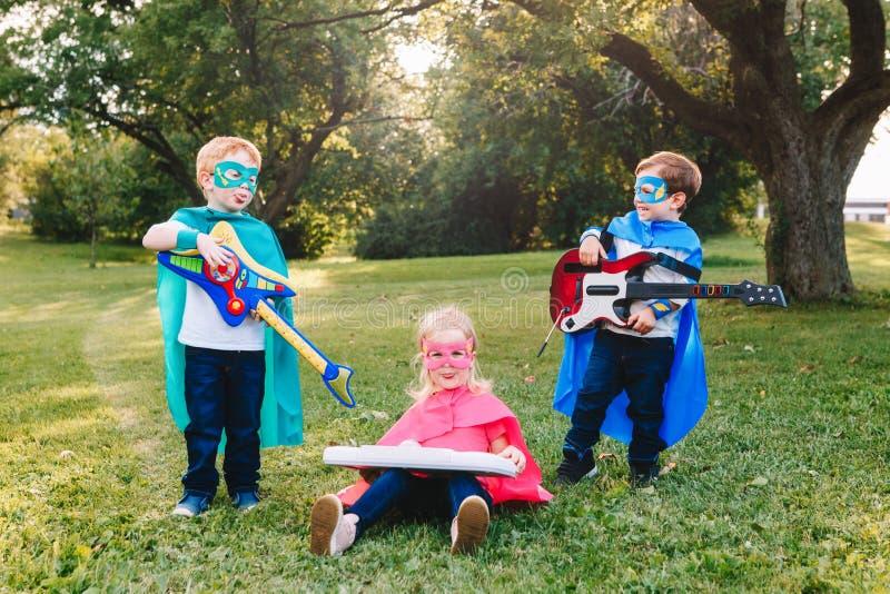 Preschool Caucasian children playing superheroes. Cute adorable preschool Caucasian children playing superheroes music band rock group. Three kids friends having stock image