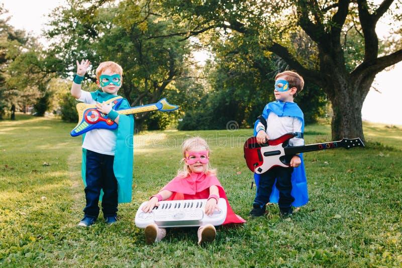 Preschool Caucasian children playing superheroes. Cute adorable preschool Caucasian children playing superheroes music band rock group. Three kids friends having royalty free stock images