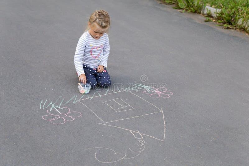 Preschool caucasian dziewczyna rysuje dom z pisze kredą obraz royalty free