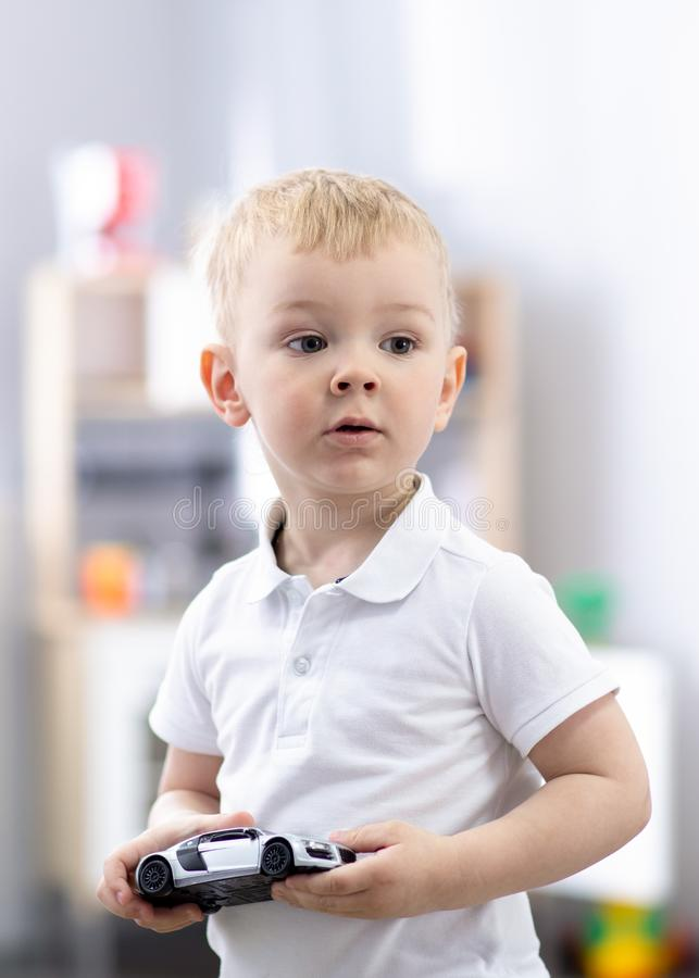Preschool boy playing with toy car at home or daycare. Educational toys for preschool and kindergarten child. Preschool child boy playing with toy car at home royalty free stock image