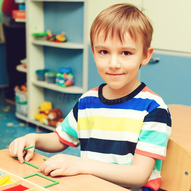 Preschool child playing intellectual toys. Preschool education and development. Smiling little boy sitting at table and plays with. Color sticks. Toys for stock photography