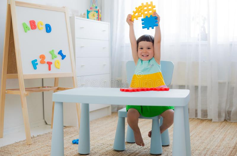 Preschool child 3 years playing with colorful toy blocks. A 3 year old child plays at a table with colorful toy blocks. A little girl sitting happy and laughing stock image