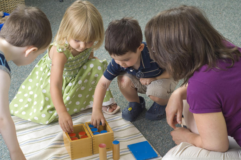 Preschool children. Children and teacher learn while playing with different shapes at the preschool class stock photos