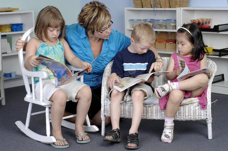 Preschool children. Teacher assists preschool boy and girls while they read books during their class stock photography