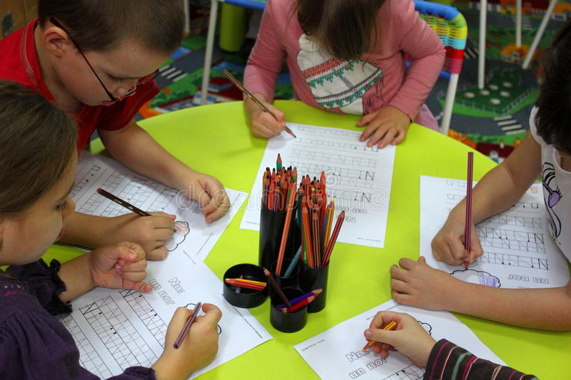 Preschool children in activities. Preschool children writing on the table in classroom at activities in a kindergarten from Bucharest, Romania royalty free stock photography