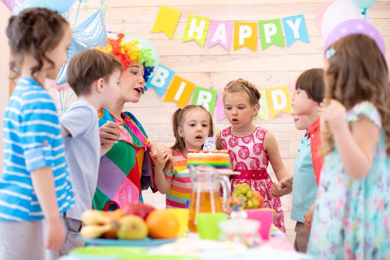 Children holding by hands and blowing candle up. Little kid girl 5 years celebrating her birthday together with friends. Preschool children holding by hands and royalty free stock photo