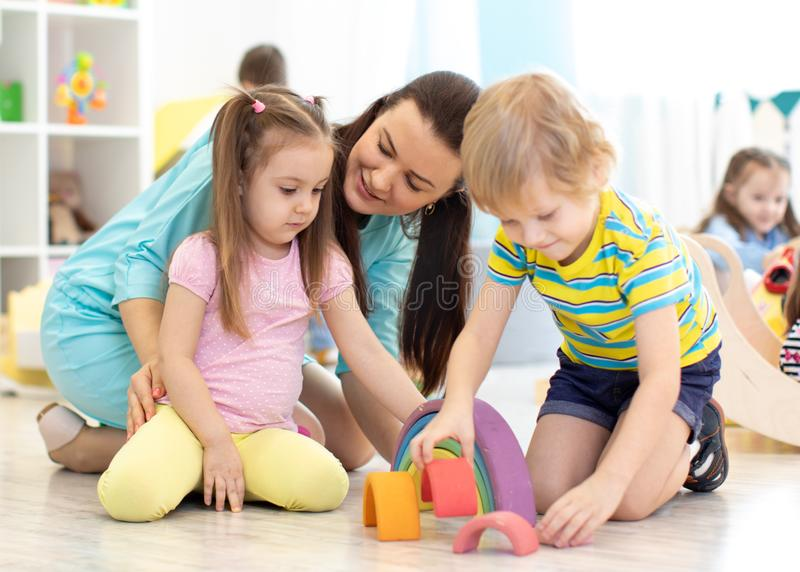 Preschool children and kindergarten teacher playing with toys royalty free stock photography