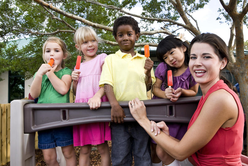 Preschool children on playground with teacher stock photo