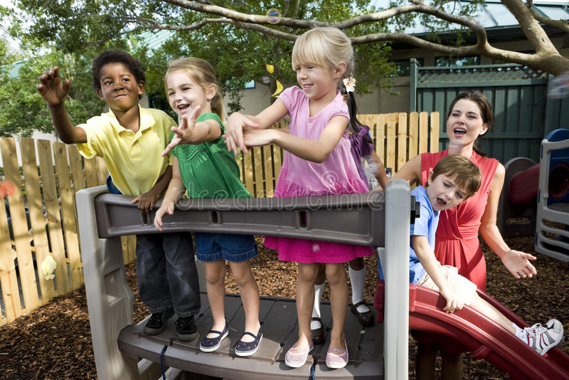 Preschool children on playground with teacher. Diverse group of preschool 5 year old children playing in daycare with teacher royalty free stock images