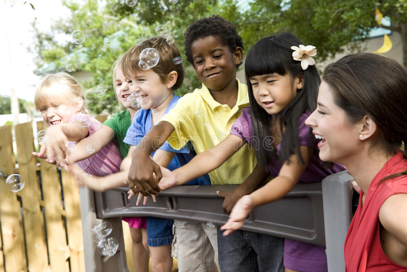 Preschool children on playground with teacher stock images