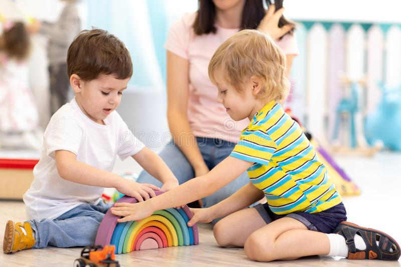 Preschool children playing with colorful wooden toys at kindergarten stock photos