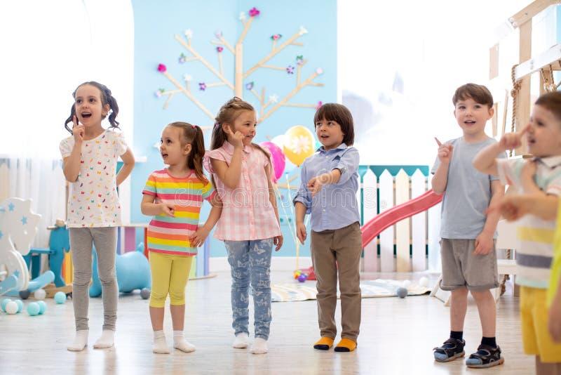 Preschool children standing on floor in kindergarten or daycare centre. Emotional kids having fun indoors, playing games. Preschool children standing on floor in royalty free stock photos