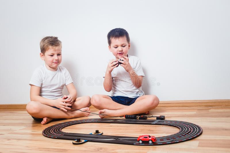 Preschool children in white t-shirts playing with a toy track and cars royalty free stock photography