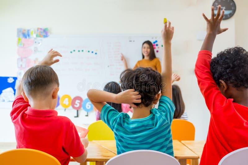 Preschool dzieciaka podwyżki ręka do odpowiedź nauczyciela pytania na whitebo fotografia royalty free