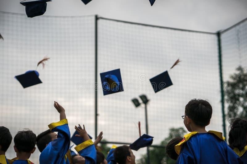 Preschool dzieciaki jest ubranym kończącego studia smokingowego miotanie nakrywają i dyplomata w niebie w kończącym studia święto obraz stock