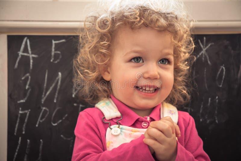 Preschool dziecka dziewczyny uczenie mądrze abecadło naprzeciw blackboard zdjęcie royalty free