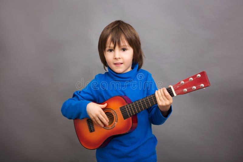 Preschool dziecko, bawić się małą gitarę, odizolowywał wizerunek zdjęcia stock