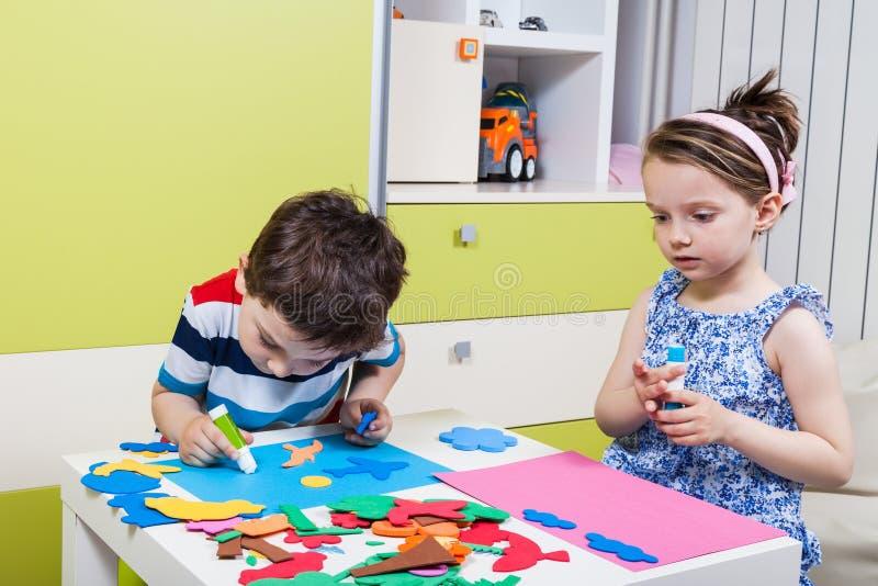 Preschool dziecko tworzy obrazek z piankowymi kształtami fotografia stock