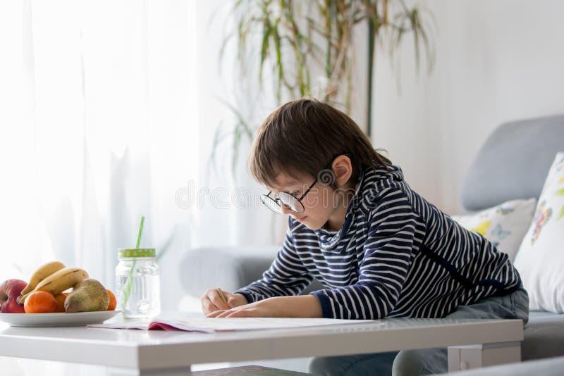 Preschool dziecko z szkłami, pisze pracie domowej w domu obrazy royalty free